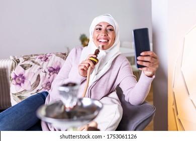 Muslim woman smoking shisha at home and taking a selfie with her mobile phone. Muslim young woman enjoying while smoking nargile. Arab girl smoking Hookah