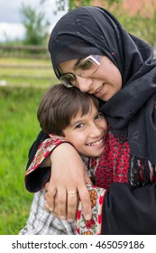 Muslim woman with son in countryside