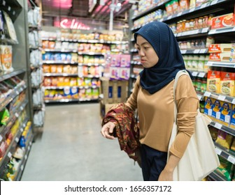 A muslim woman standing in an aisle of a groceries shopping mall