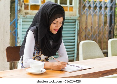 muslim woman student in black hijab writing on note book while studying in class.