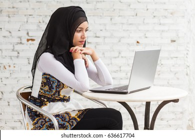 muslim woman student in black hijab writing watching on note book on old brick background.