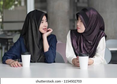 muslim woman talking; islam  or islam women chatting, talking with her friend; asian 20s woman model with hijab or islamic head scarf