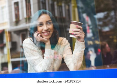 Muslim Woman Talking on Mobile Phone in a Cafe