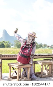 Muslim woman traveler enjoy panorama view of beautiful Asian scenery of nature field cottage. Coffee shop in rice field. Trip to Thailand.