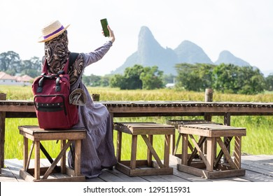 Muslim woman traveler enjoy taking photo with smart phone of beautiful Asian scenery of nature field cottage. Coffee shop in rice field. Trip to Thailand.