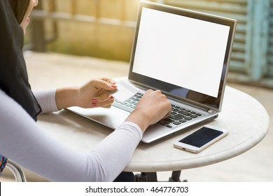 Muslim woman using laptop computer with blank copy space screen while sitting in cafe,flare sun.