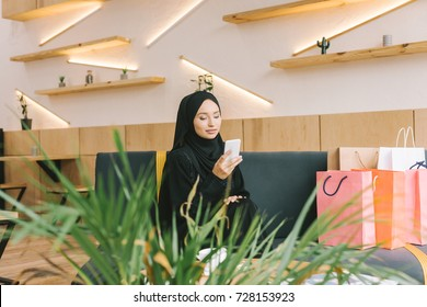 muslim woman using smartphone in cafe with shopping bags