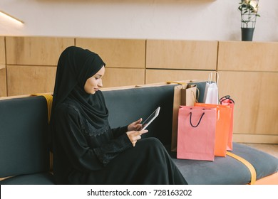 muslim woman using tablet in cafe with shopping bags standing on couch