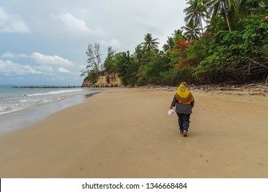 Muslim woman walking in hijab on paradise white sand Tanjung Kubong tropical beach located at the northern tip of Labuan Island. It is also the place where the famous chimney standing.