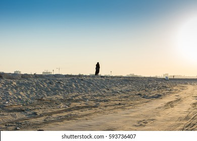 A Muslim woman walking on a dam at at beach towards to the sun in the morning in Dammam, Saudi Arabia