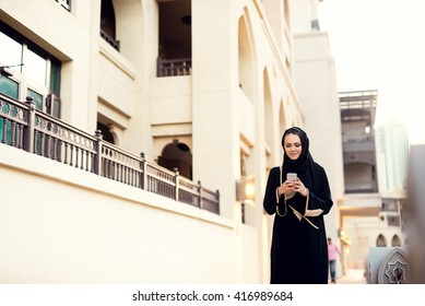 Muslim woman walking and typing message.