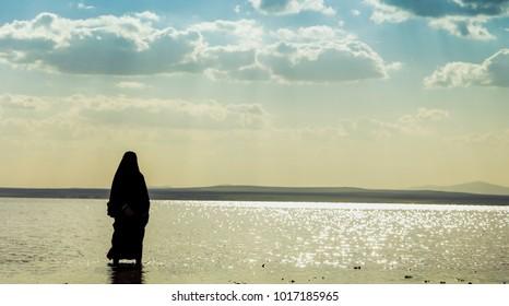 Muslim woman wearing a black hijab walking on Lake Tuz,Turkey.