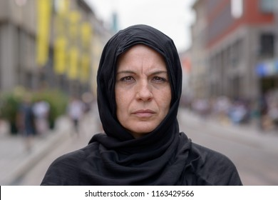 Muslim woman wearing a head scarf or hijab in an urban street staring thoughtfully at the camera in a close up head and shoulders portrait