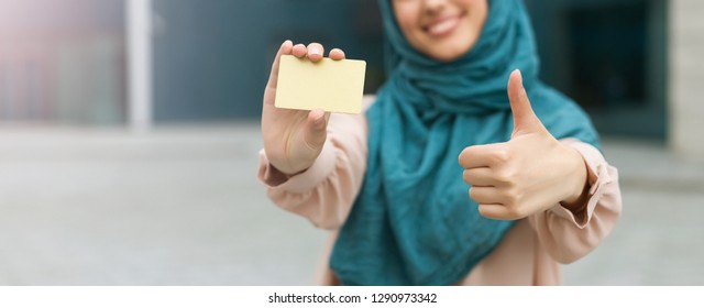 Muslim woman wearing hijab holding credit card with thumbs up gesture.