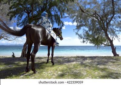 Muslim woman wearing hijab riding horse on puru kambera beach, sumba, indonesia