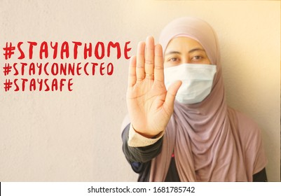 Muslim woman wearing mask showing stop sign to stop corona virus with hashtag stay at home stay connected and stay safe