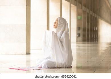 Muslim woman wearing prayer veil, praying for Allah, muslim god