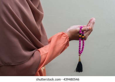 A Muslim woman wearing traditional malay clothes with hijjab and rosary, praying in the mosque, Muslim woman raising hand pray