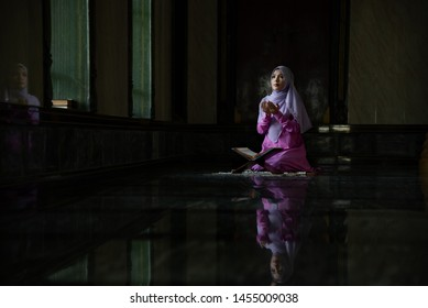Muslim woman who is wearing the Islamic long hijab khimar was praying and doing dua at the mosque for Islamic religious ceremony.