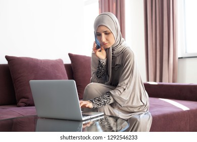 Muslim woman working at a cafe and using laptop and phone.
