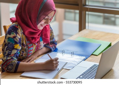 Muslim woman working with computer in library.