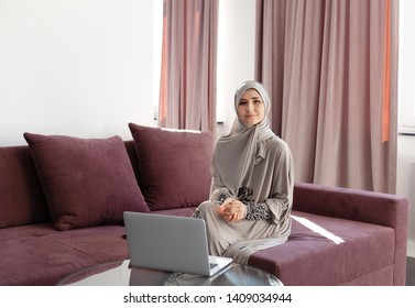 Muslim woman working at home and using laptop and phone.