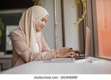 Mujer musulmana trabajando en laptop. Mujer musulmana asiática trabajando en el cargo.