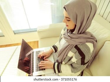 Muslim woman working on laptop, overhead shot.