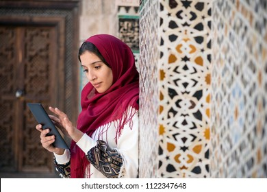 Muslim woman working on tablet in traditional clothing with red headscarf on her head beside a traditional arabesque Moroccan wall