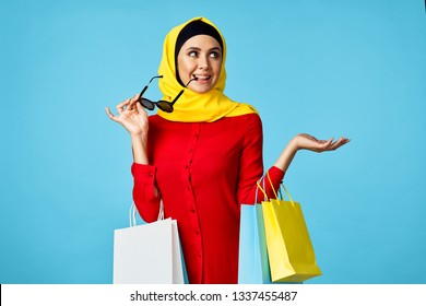 muslim woman in a yellow veil with glasses on a blue background
