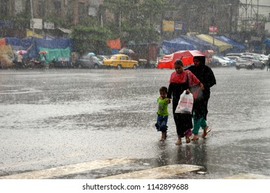 Muslim women along with her son wade through the street during the monsoon rain on July 23, 2018 in Calcutta, India.
