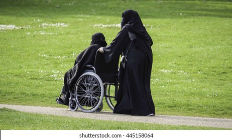 Muslim women in burkas in a park - one pushing the other in a wheelchair
