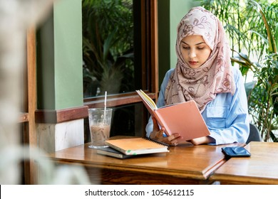 Muslim women hijab  reading book at cafe