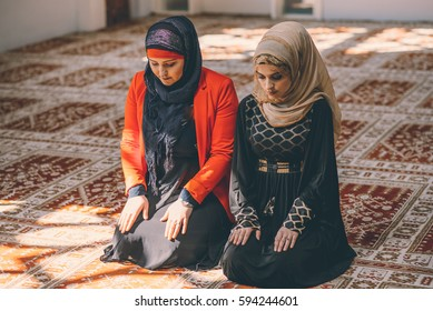 Muslim women kneeling in prayer