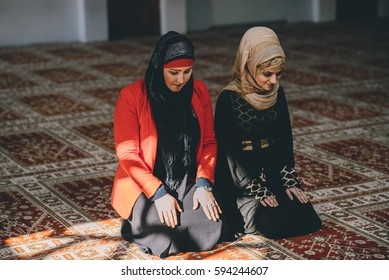 Muslim women kneeling in prayer