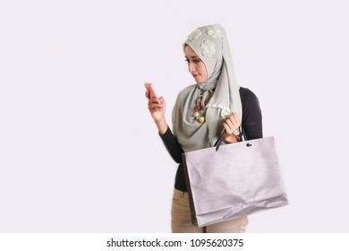 muslim women standing holding smartphone and shopping bag. young muslim woman using smarphone with blank area for copyspace.
