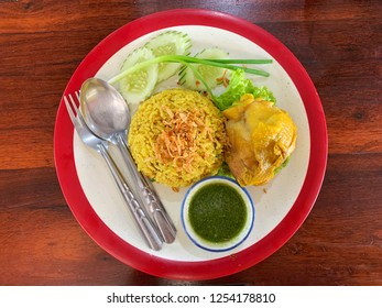Muslim yellow rice with chicken on wooden table, top view food.