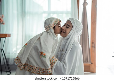 muslim young child kiss her mom after praying together