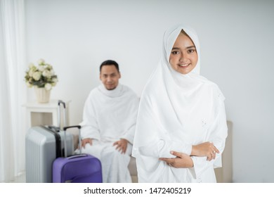 muslim young woman standing in front of her husband wearing white traditional clothes for Ihram before umrah