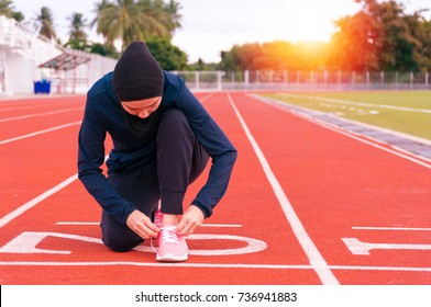 Muslim young woman wearing dark sport clothes and hijab, tying pink shoe at starting point on running track before start run training in the morning with sunrise and trees in background.
