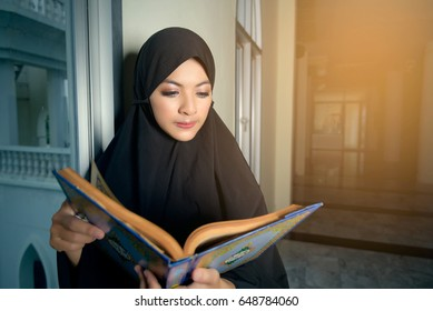 Muslim young women with black hijab reading quran in mosque, Muslim people respect islam, Islam is religion