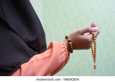 A Muslimah wearing traditional malay clothes with hijjab and rosary, praying in the mosque, Muslim woman raising hand pray. TONE images and background. shallow D.O.F