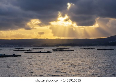 Mussel aquacultuere rafts under sunlights of stormy sunset in Arousa estuary