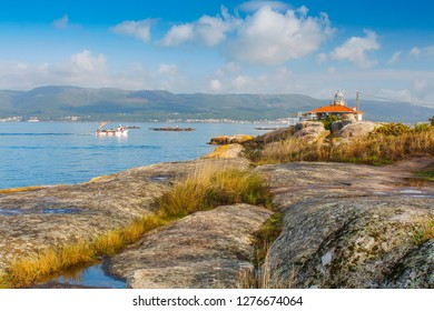 Mussel aquaculture rafts and auxiliary boat sailing neas Punta Cabalo lighthouse in Arousa Island