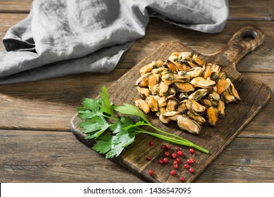 Mussel meat on a wooden Board on a wooden table. Rustic style