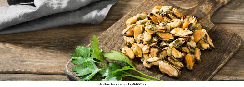 Mussel meat on a wooden Board on a brown wooden table. Clams on the serving Board. Rustic style. Banner with space for text