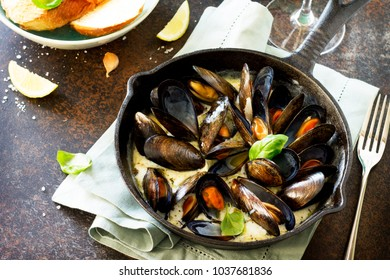 Mussels boiled in a sauce of white wine, served with toast and lemon. Gourmet italian cuisine.