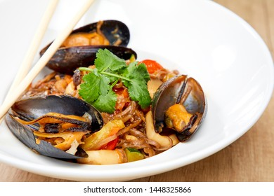 mussels with buckwheat noodles on wooden table