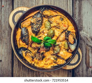 mussels with cheese sauce, in a frying pan, wooden background