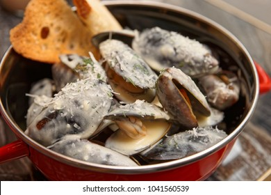 Mussels cooked with creamy sauce and served in metal casserole, close-up